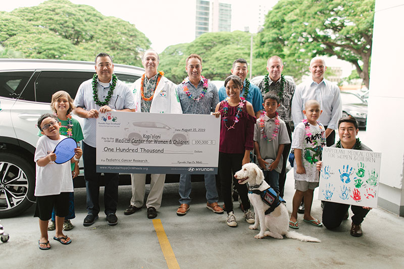 Pediatric cancer patients, Kapiolani's Dr. Darryl Glaser and Hyundai Hawaii auto dealer representatives with ceremonial check for $100,000