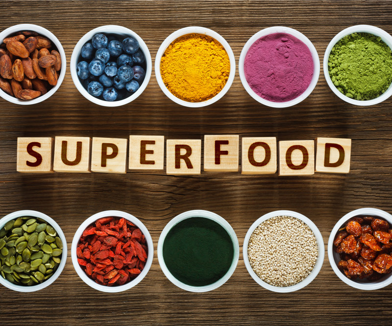 the word Superfoods spelled out in blocks surrounded by measuring cups of popular superfoods and supplements