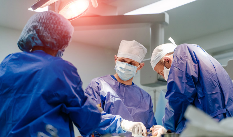 Three doctors in surgical scrubs in operating room