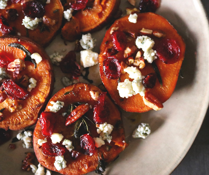 a plate of sliced sweet potato rounds topped with crumbled blue cheese, chopped pecans and dried cranberries