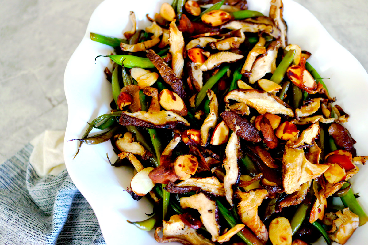 a white serving plate of Garlicky Green Beans topped with crispy mushrooms and almonds