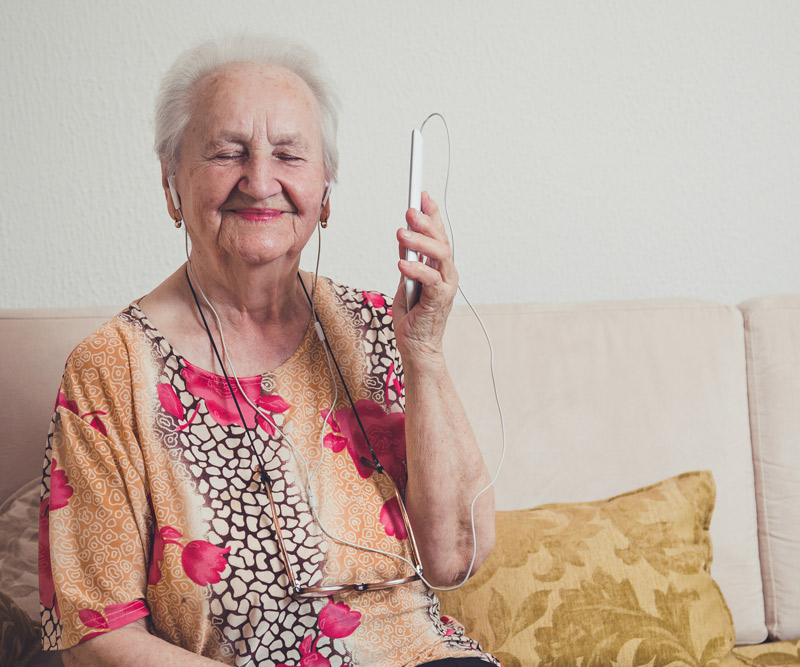 old woman sitting on couch listening to music from a mobile phone