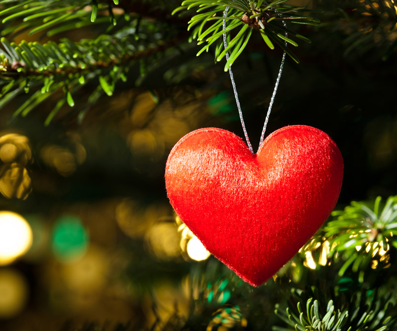 a felt heart ornament hangs on a Christmas tree