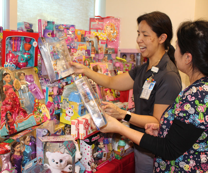 two women sort through a large collection of toys for children in a conference room at a medical center