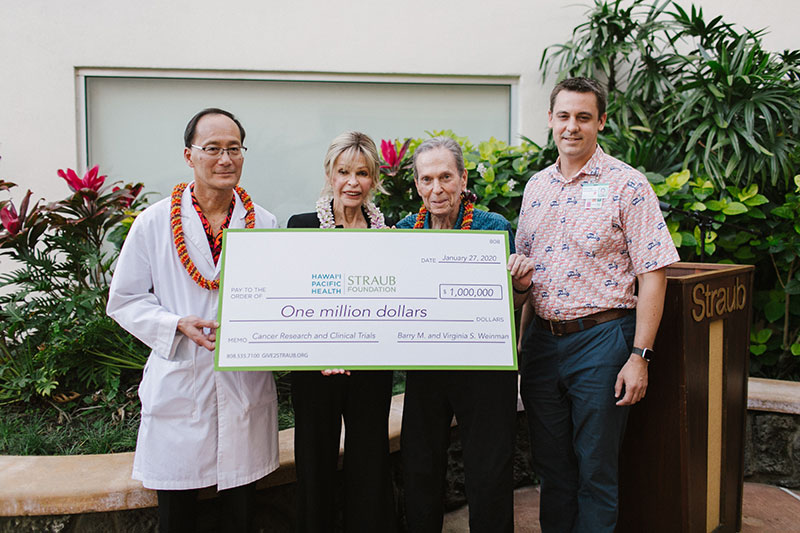 Four people holding ceremonial check for $1 million