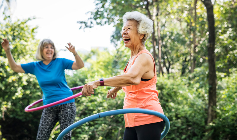 two elderly women happily laughing and playing with hula hoops outdoors