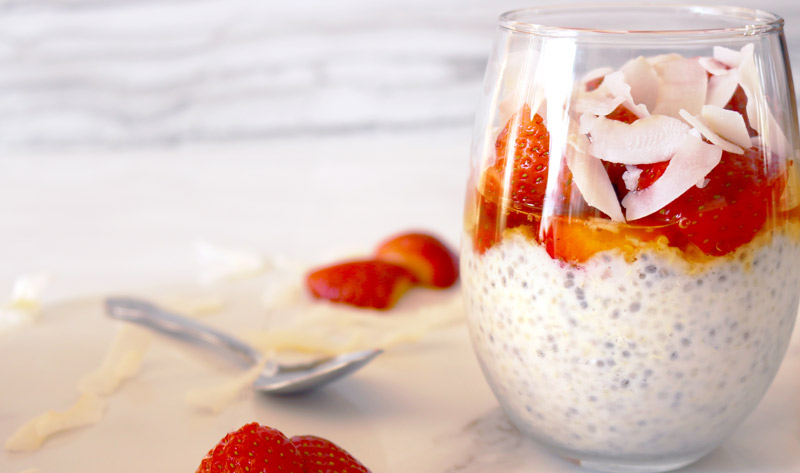 a clear glass layered with chia seed-quinoa pudding, honey, strawberries and coconut flakes on a marble counter top with a spoon and strawberry slices and coconut flaked scattered on top