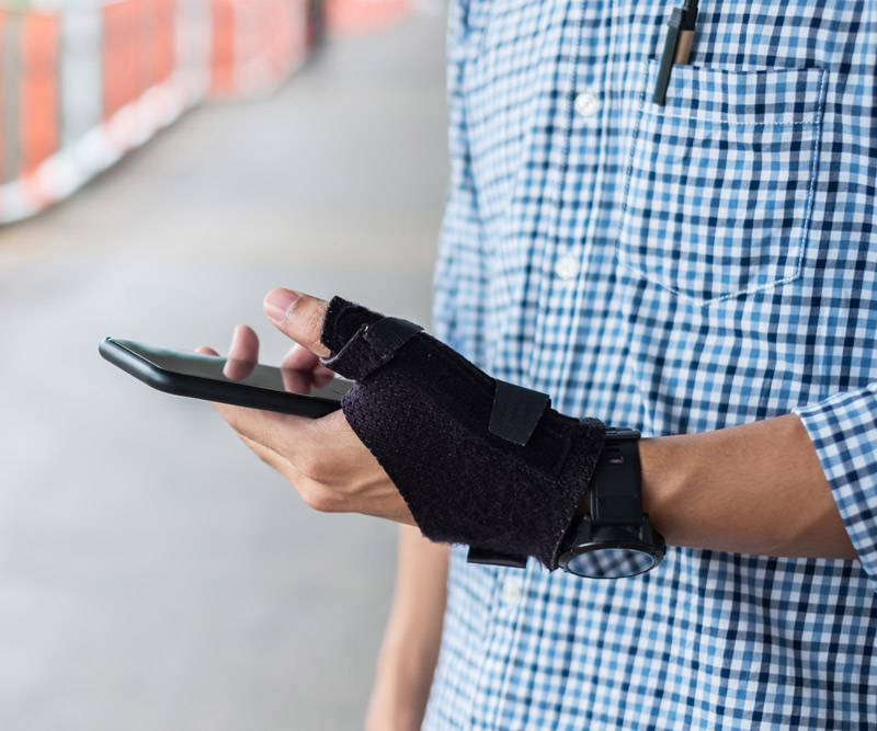 man with brace on wrist texting
