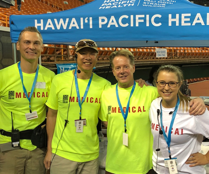 three men in neon green volunteer shirts and a woman in a white volunteer shirt stand in front of a blue pop-up tent that says Hawaii Pacific Health