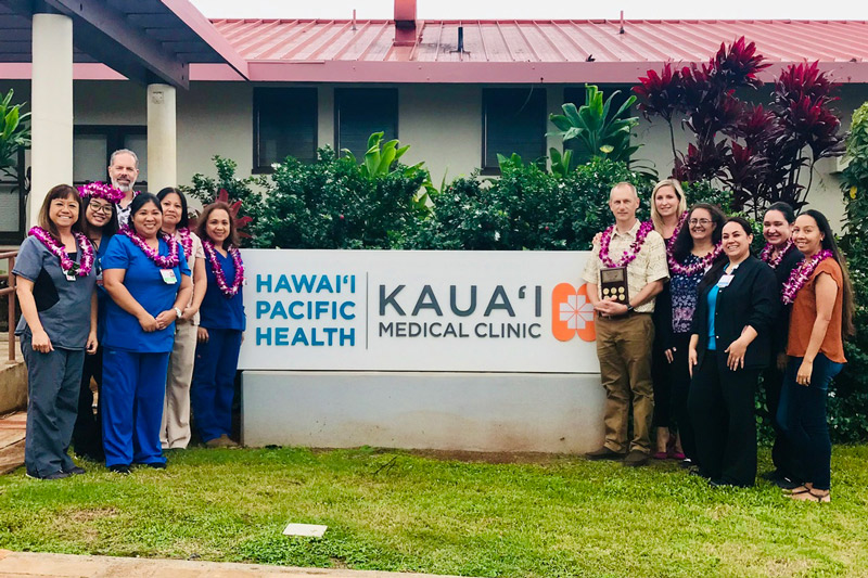 group of people wearing lei and holding an award stand in front of Kauai Medical Clinic sign