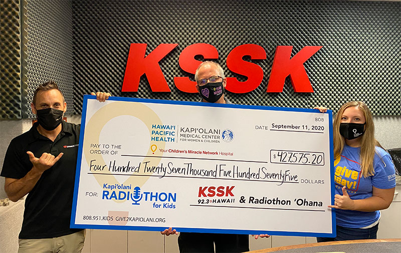 Three people holding ceremonial check in front of KSSK radio sign