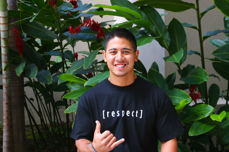 a guy wearing a respect shit smiling and showing a shaka
