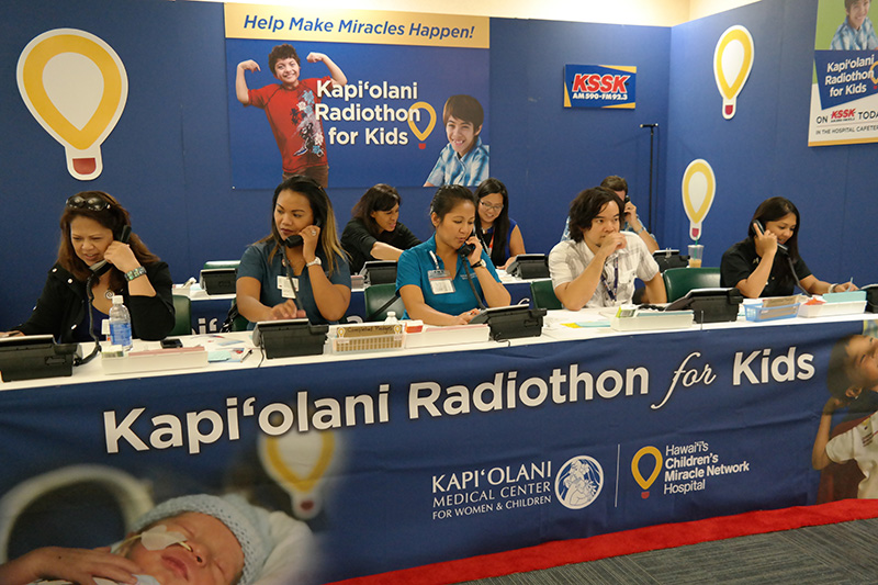 group of people taking phone calls at a children's miracle network radiothon event