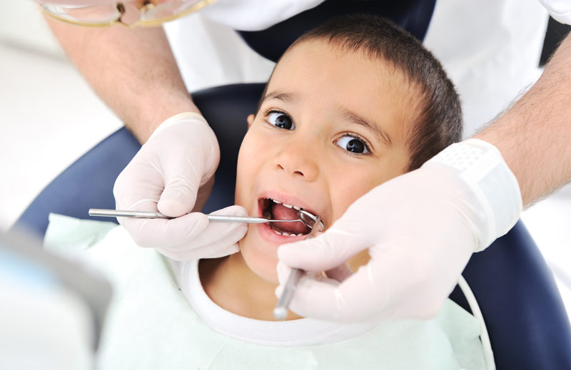 a young child with dental tools in the mouth
