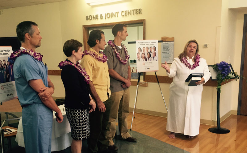 group of people wearing leis at a ceremony