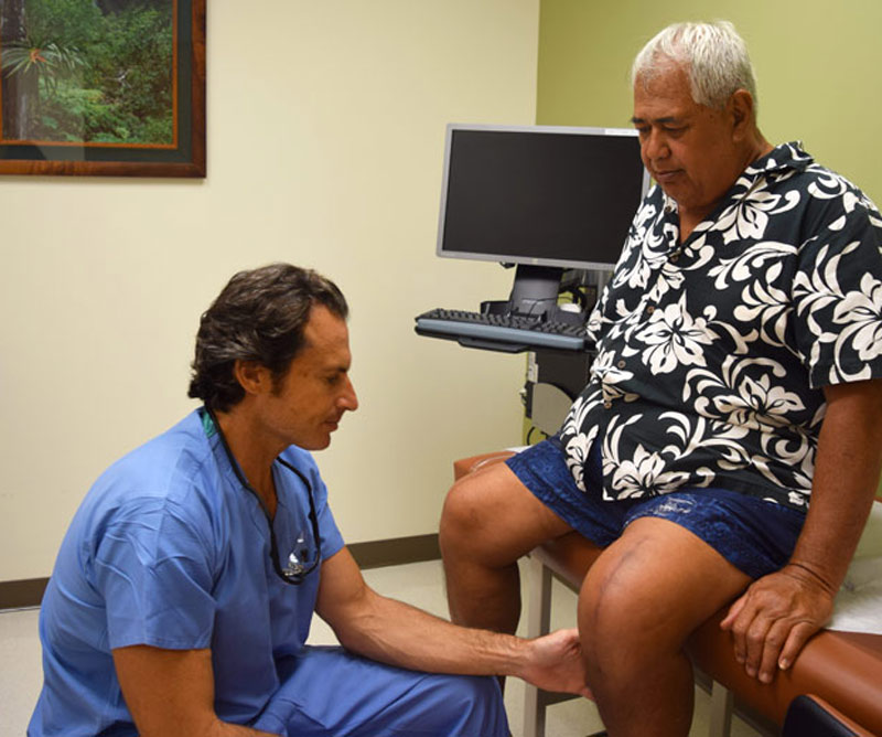 Patient getting his knee examined by doctor