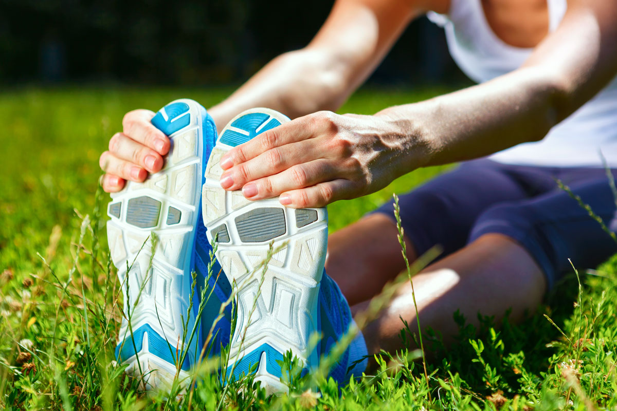 a runner stretching in a grassy field