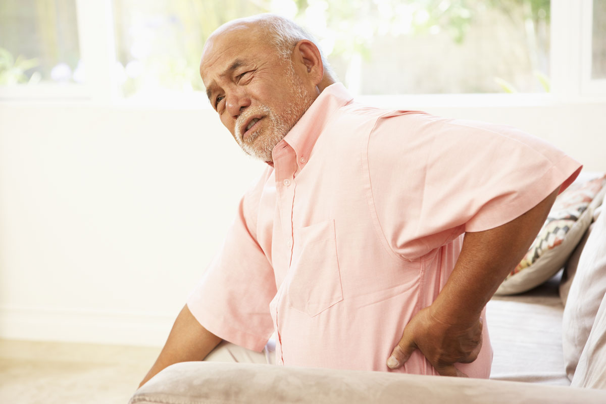 an older man sitting in a chair touching his lower back