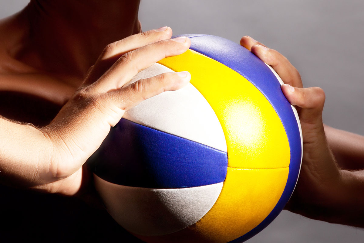 athlete holding a volleyball with both hands