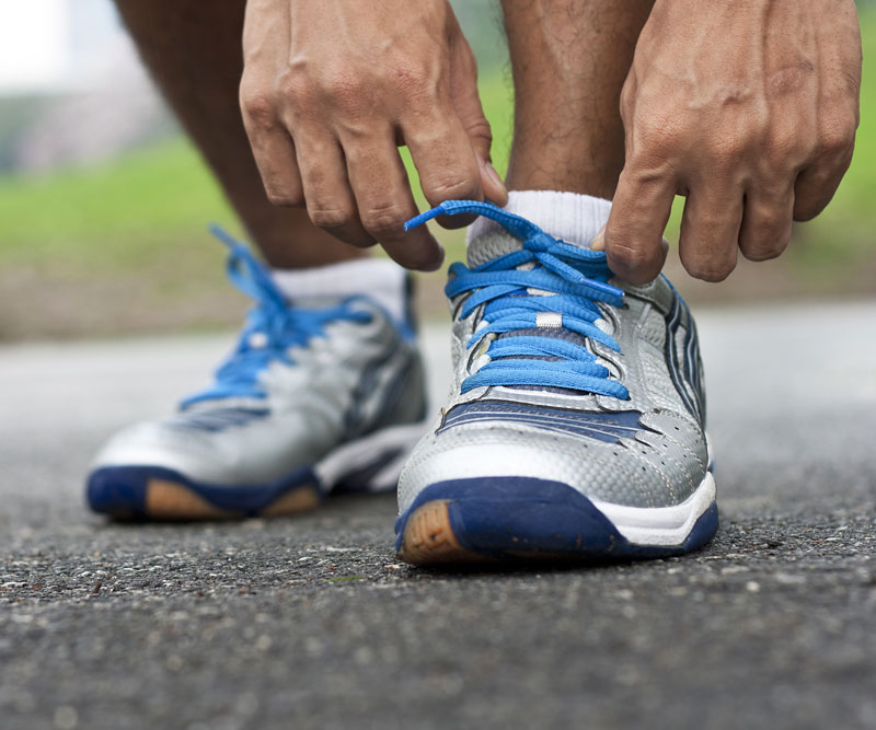 a close up of a runner adjusting their shoes