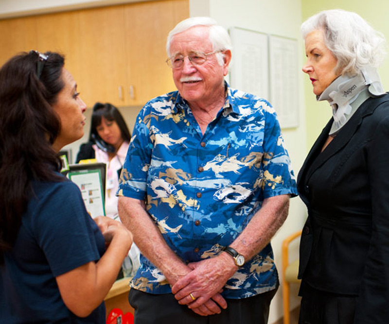 elderly couple speaking with a caretaker