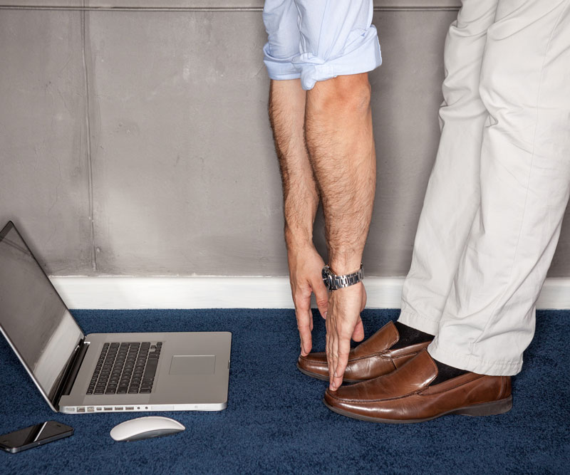 a laptop on the ground next to a person touching their toes