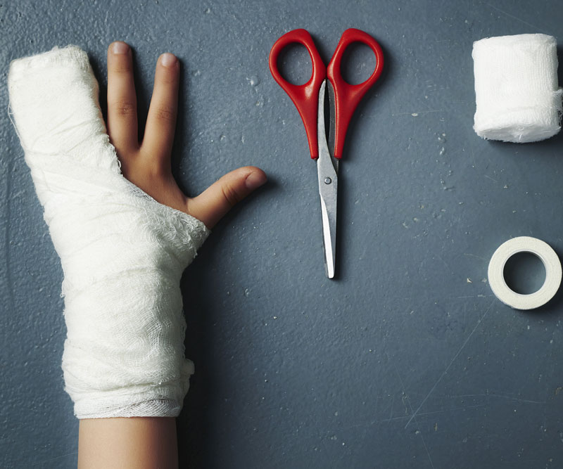 an illustrated injured child hand reaching scissor