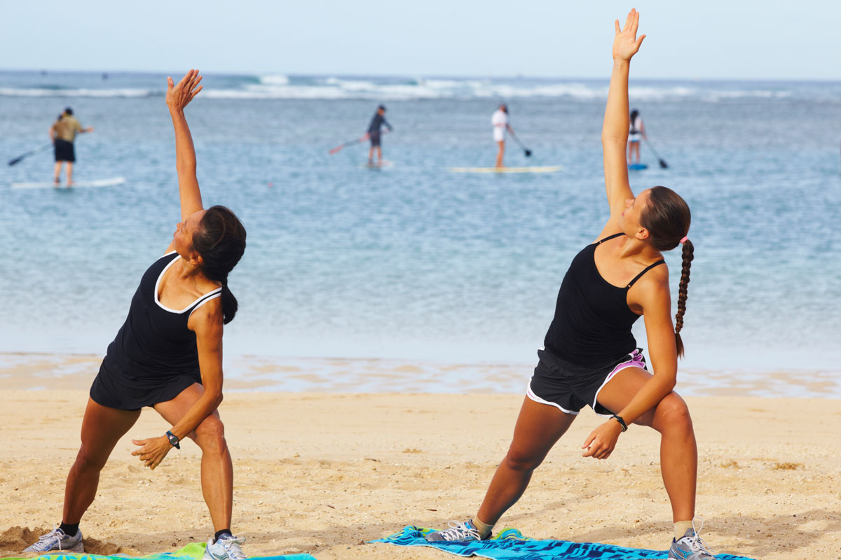 two people on the beach doing yoga