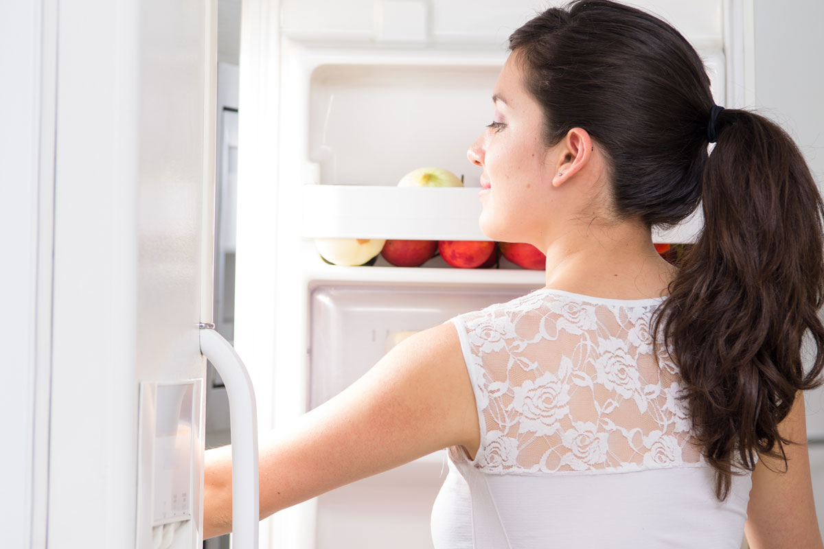 a lady looking inside a refrigerator