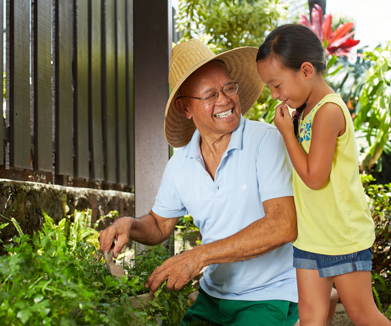 a grandfather wearing a big hat and his granddaughter work in a garden smiling