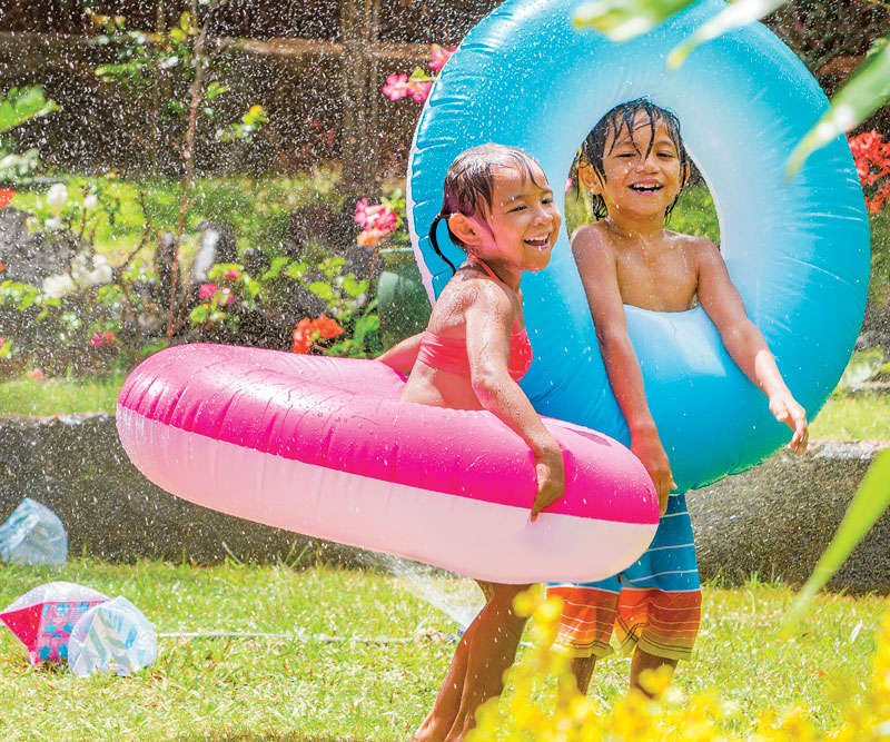 two kids playing in the yard with a sprinkler and blow up pool toys