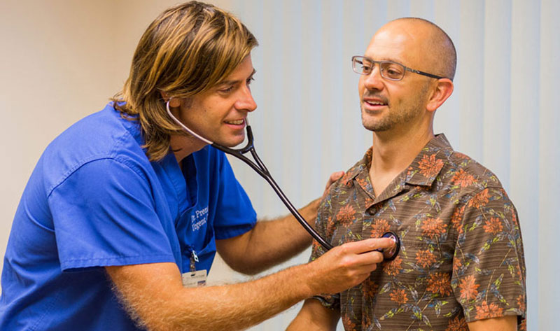 A doctor uses a stethoscope to check a patient's heart beat