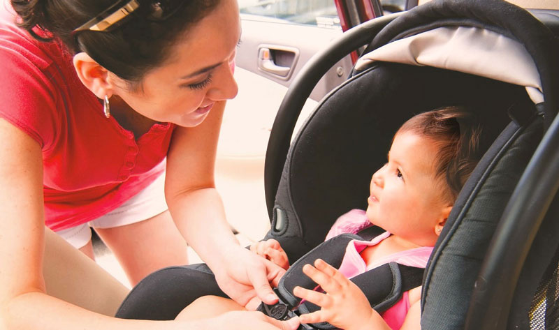 a women securing child safety seat