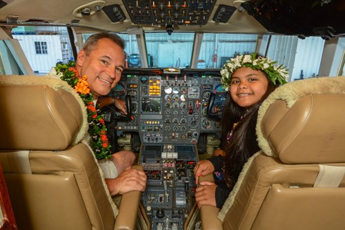 Emergency Airlift CEO Ed Langerveld sits in the cockpit of the Falcon 500 with 'co-pilot' Ashlyn, who was transported from Hawaii to Seattle Children's Hospital to receive emergency treatment for a heart condition.