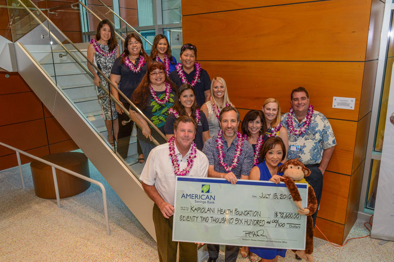 American Savings Bank employees standing on stairs holding up a large donation check