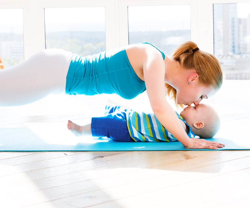 mom doing push -ups while kissing a baby