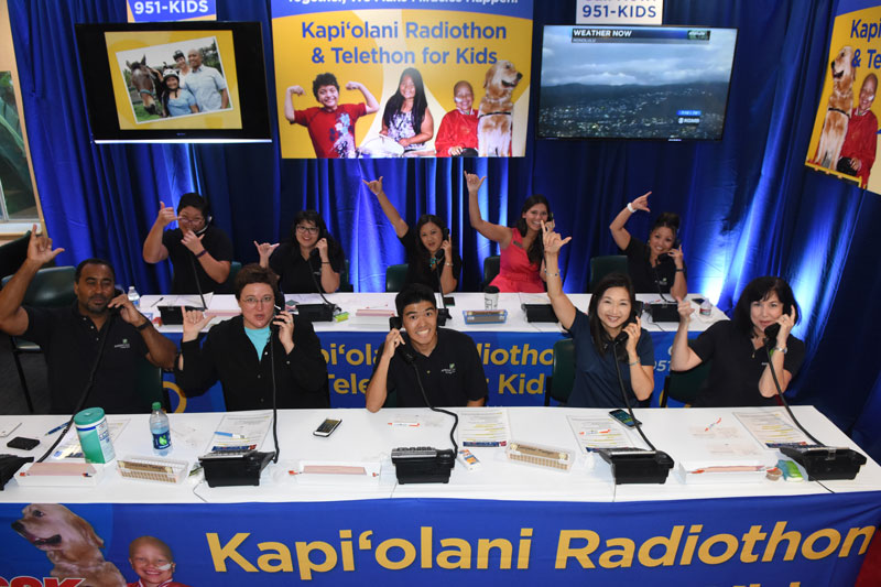 group of kids sitting at a table answering phones for a radiothon