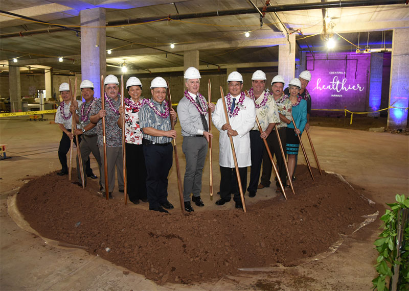 a group at a groundbreaking with shovels standing near a large mound of dirt