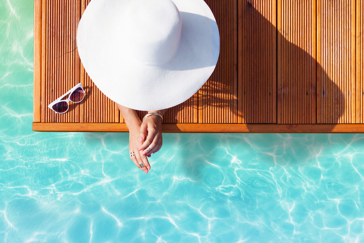 woman with sunhat sitting by the pool