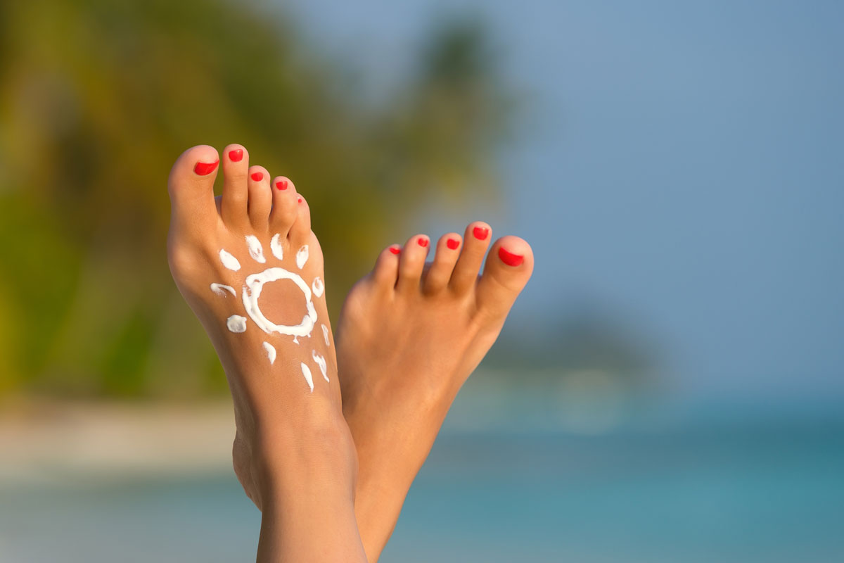 two feet with a sun painted in sunscreen on one of them