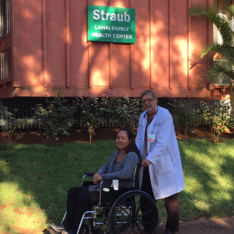 a patient in a wheelchair outside the hospital with a medical professional pushing her