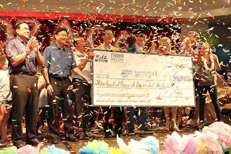 a group celebrating on stage with a large check with confetti falling down
