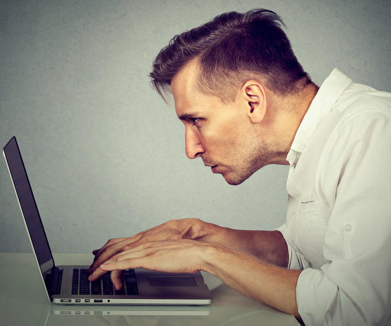 man crouched uncomfortably in front of his laptop