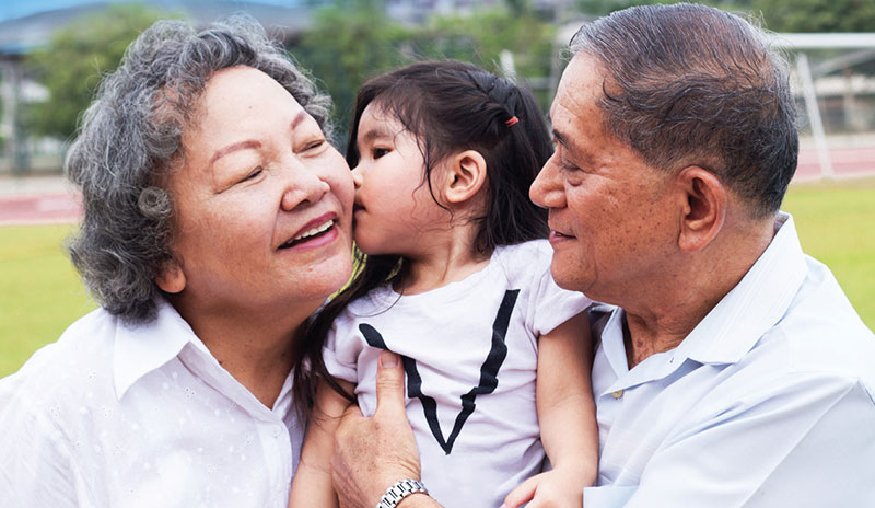 Photo of a little girl held by her grandfather kissing her grandmother
