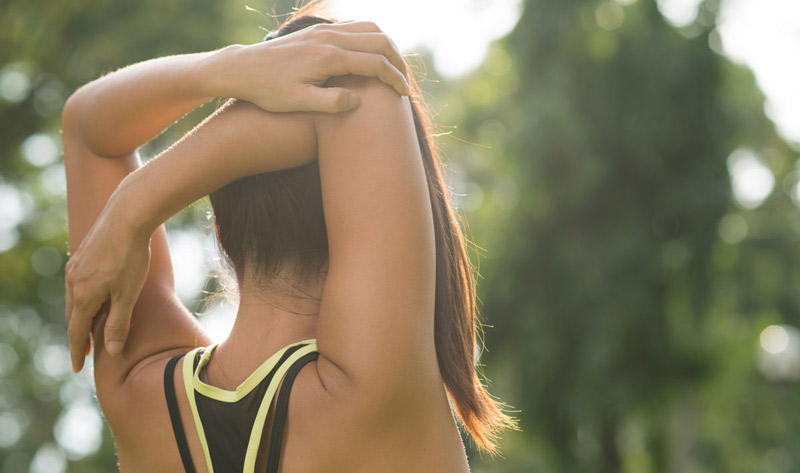 Young athletic woman stretching her arms over her head