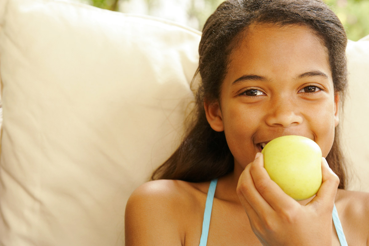 young girl taking a bite out of an apple
