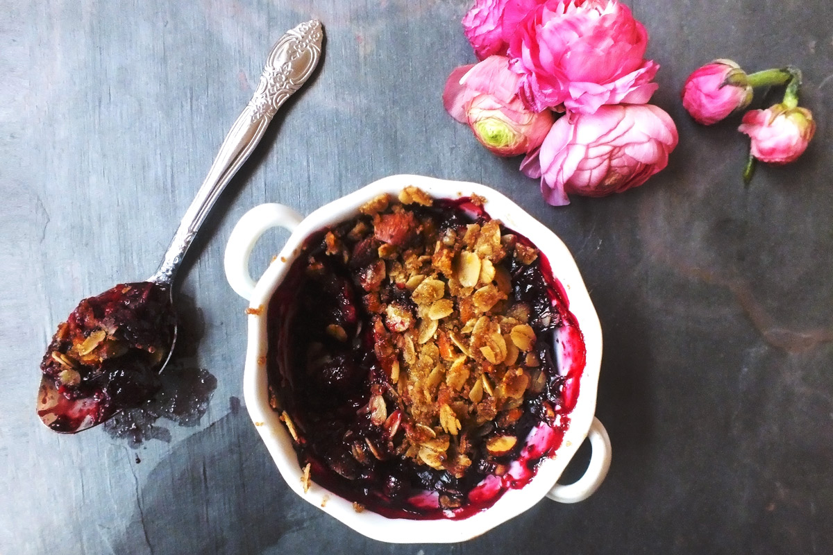 a white ramekin of Old-Fashioned Fruit Crumble with a spoonful of crumble taken out of it sits on a slate counter top that has been decorated with a bunch of pink flowers