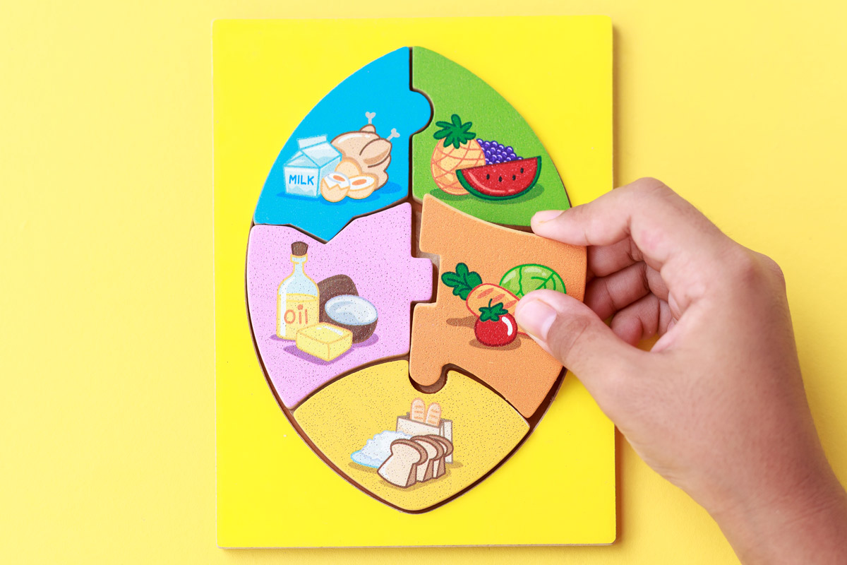 Child building a puzzle out of different food types