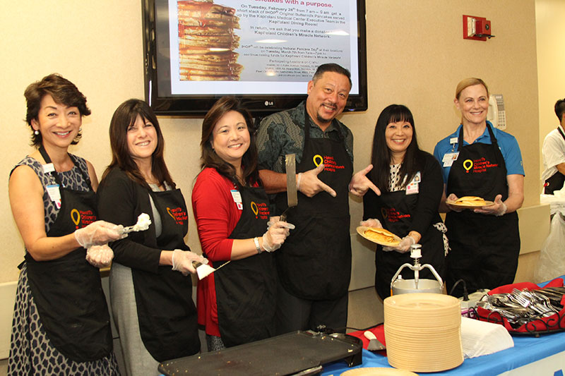 Photo includes (l to r) Dawn Ching, Laura Bonilla, Carrie Ann Tsutsui, Joel Emperador, Mavis Nikaido and CEO Martha Smith, flipped and served more than 500 pancakes for medical center employees and visitors.