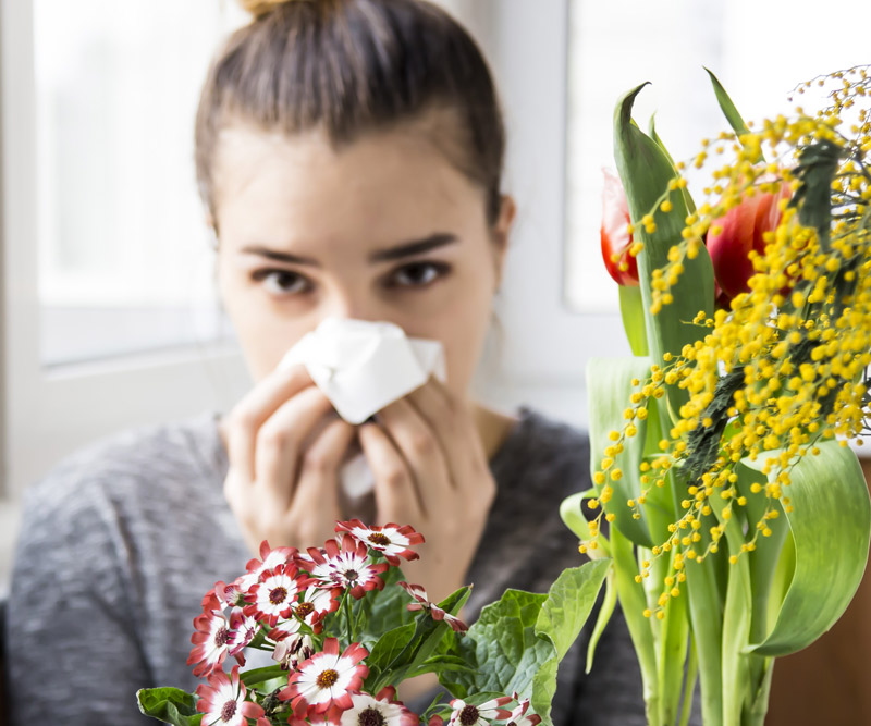 woman blowing her nose into a tissue